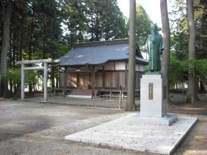 Entrada principal del Aiki Jinja, con el tori y la sala de oraciones. La estatua de O Sensei está en el primer plano.