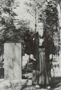 Morihei Ueshiba en Iwama junto a uno de sus Doka en un monumento de piedra en el Aiki Jinja en Iwama