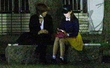 ベンチに座ってスマホを見ている二人