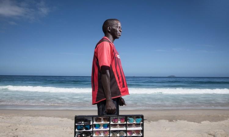 Vendedor informal de gafas en la playa