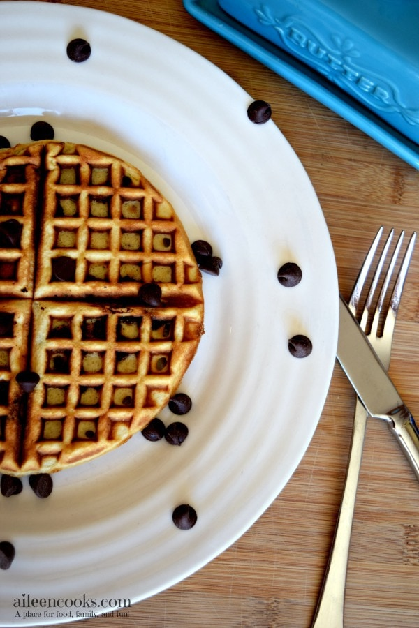 A white plate with a chocolate chip waffle on top and chocolate chips scattered the plate.