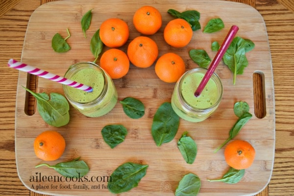 Two orange spinach smoothies in mason jars on a cutting board next to mandarin oranges and baby spinach.