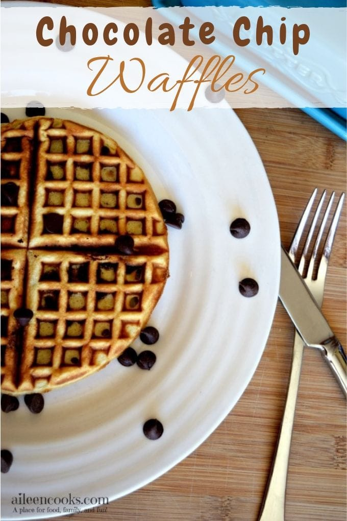 A white plate with chocolate chips waffle recipe next to a fork and knife.