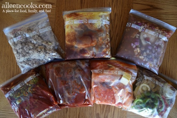 An overhead shot of 14 crockpot freezer meals frozen in ziplock bags.