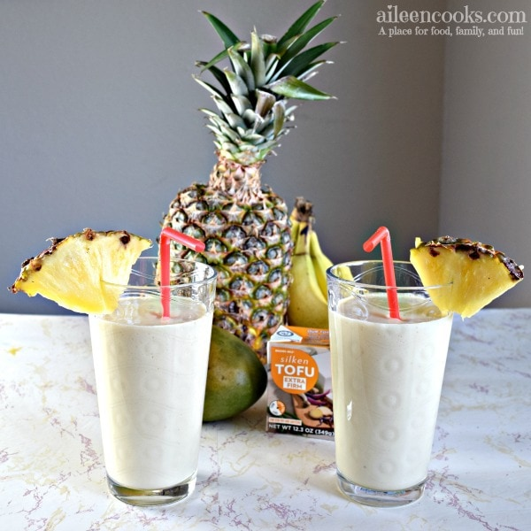 Two protein packed tropical smoothies with pineapple slices and red straws