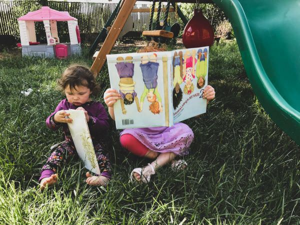 Two children reading books in a yard.