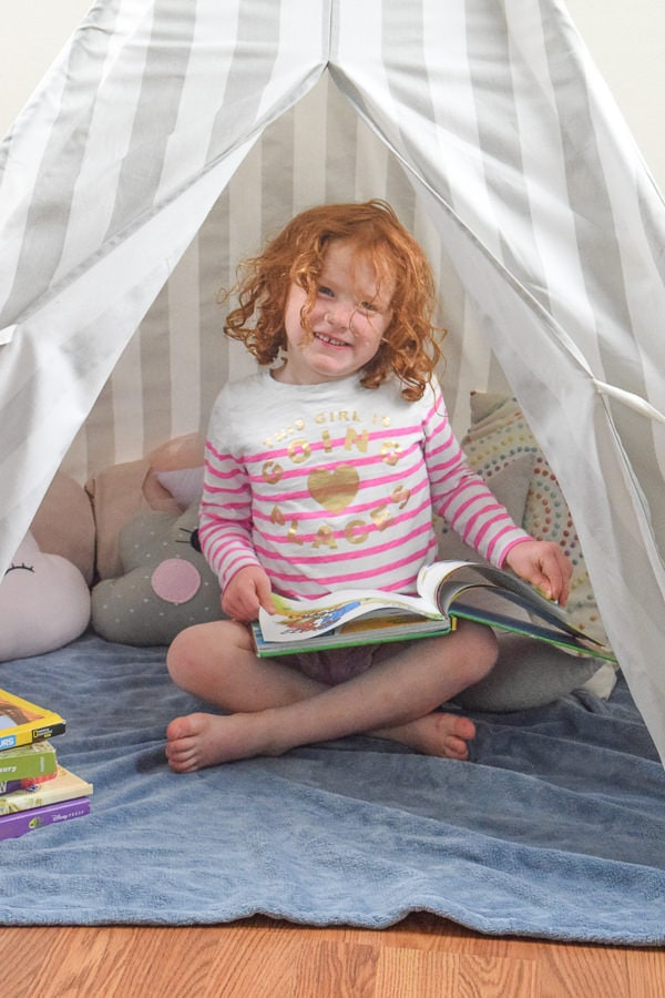 Little girl reading a book in her kids reading nook