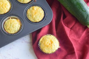 cheesy cornbread zucchini muffin on red cloth napkin next to muffin tin full of muffins and large zucchini