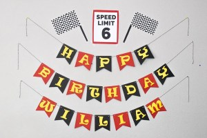 Happy Birthday William banner with a Speed Limit 6 sign and two checkered flags - all made out of paper.