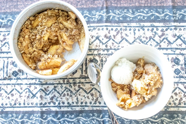 Bowl of instant pot apple crisp served with a scoop of vanilla ice cream.