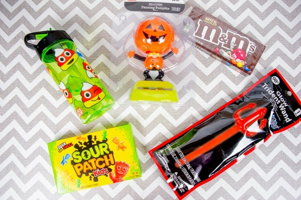 The contents of a BOO basket for a tween boy: two full sized candy bars glow stick, water bottle, and dancing pumpkin figurine.