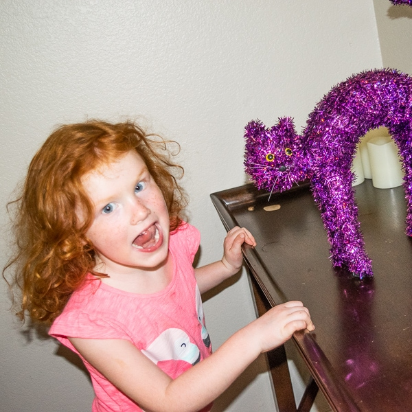 A red headed girl standing next to a purple cat decoration.