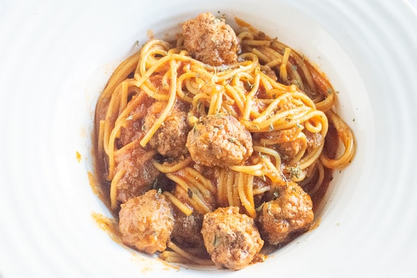 Instant pot spaghetti and meatballs served in a white wide rimmed bowl.