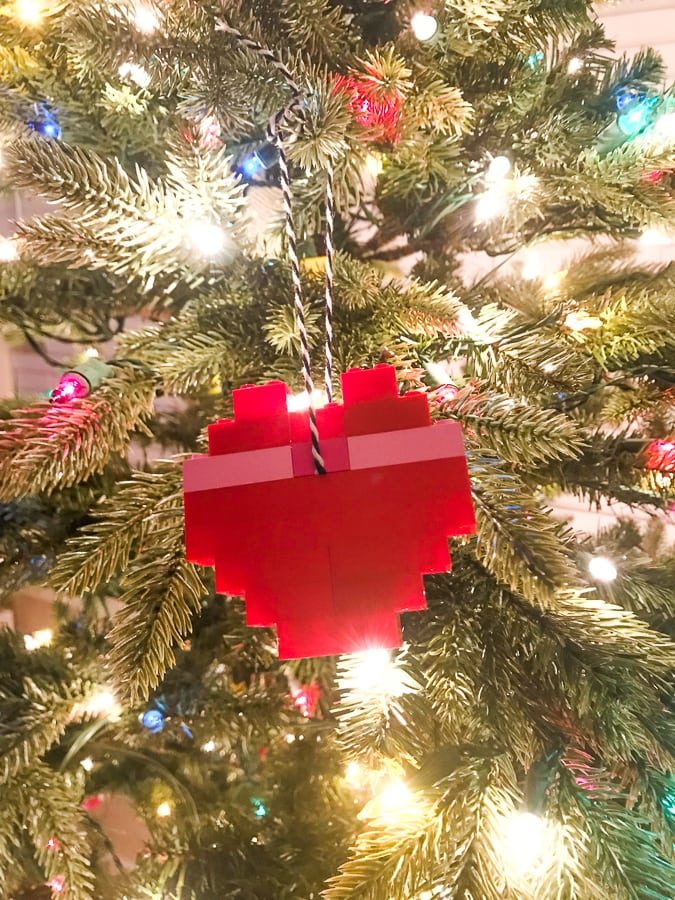 A heart shaped holiday ornament made of LEGO and hanging on a lit Christmas tree.