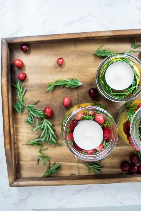 A wooden tray filled with mason jar christmas centerpieces, Rosemary, and cranberries.