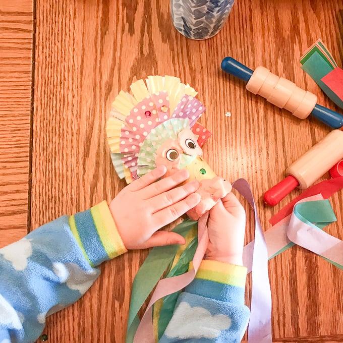 A child's hand holding a handmade dragon.