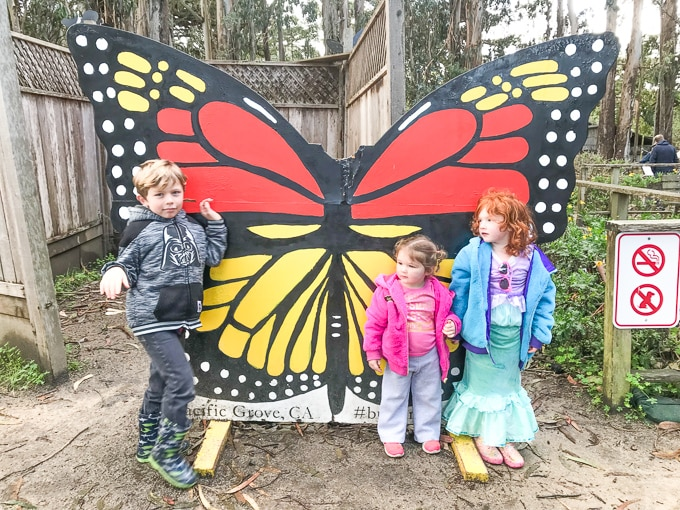 One boy and two girls standing in front of a 3-foot tall wooden butterfly at the Monarch Butterfly Sanctuary.