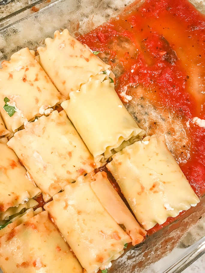 Spinach lasagna rolls placed seem-side down in a glass casserole dish.
