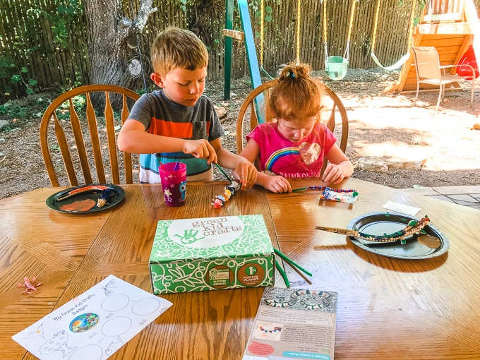 Two kids sitting outside at a wooden table completing projects from their green kid craft subscription box.