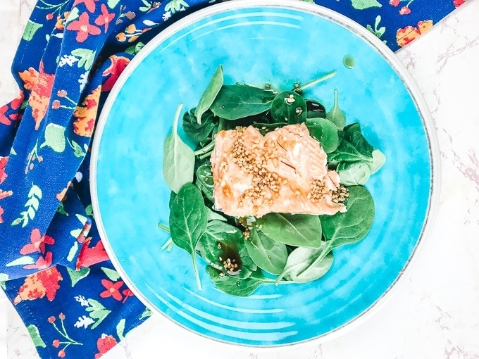 A blue plate with teriyaki salmon that was made in the instant pot.