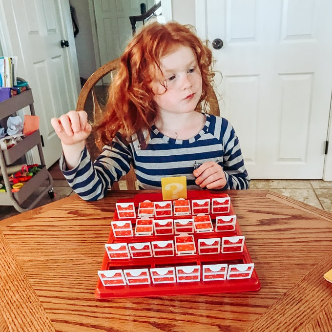 A red headed girl playing Guess Who.