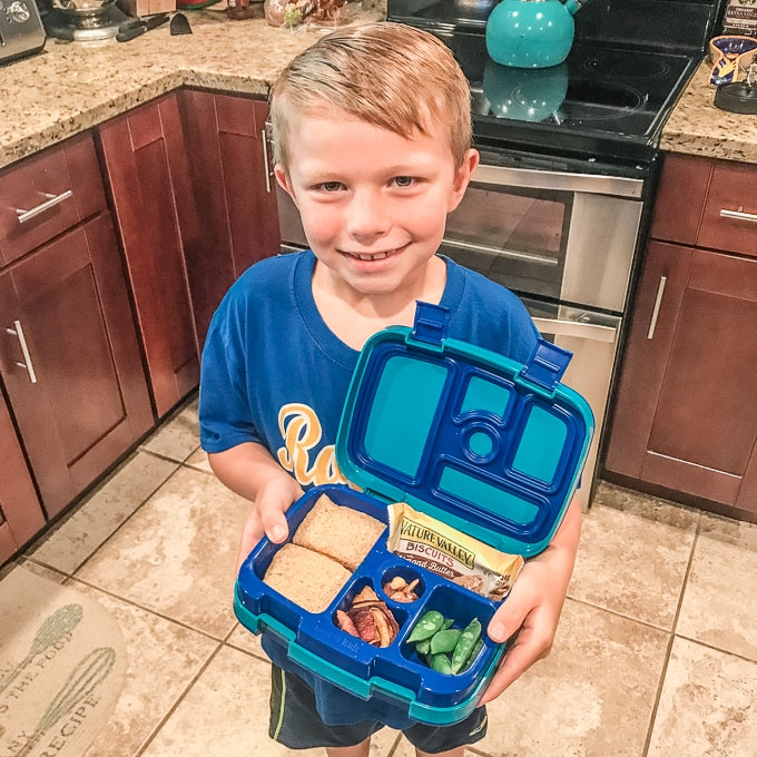 Little boy smiling and holding a bento box.