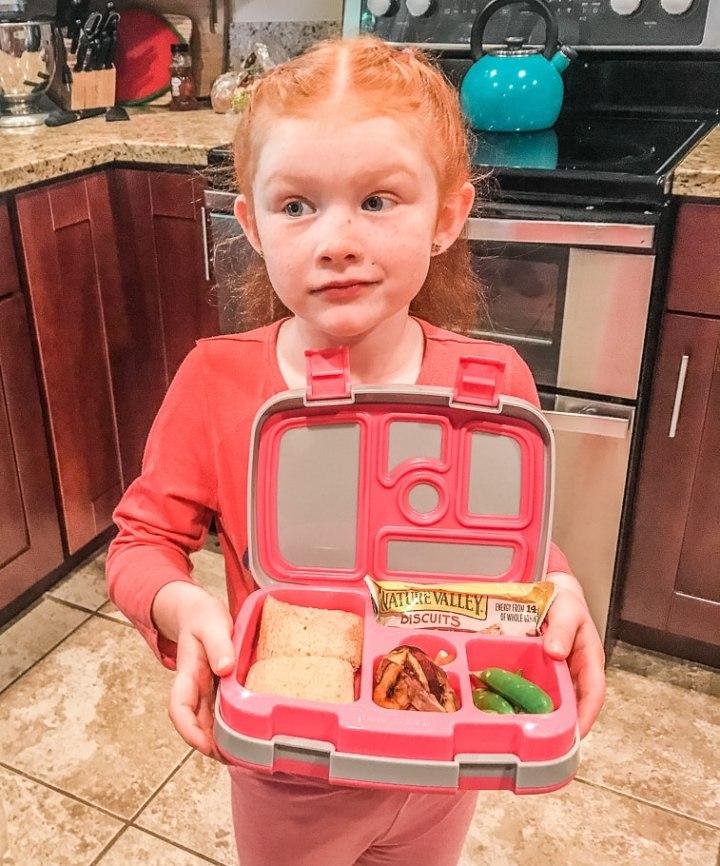 A little girl holding an open bento box.