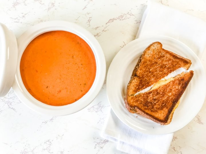 A bowl of tomato basil soup next to a grilled cheese.
