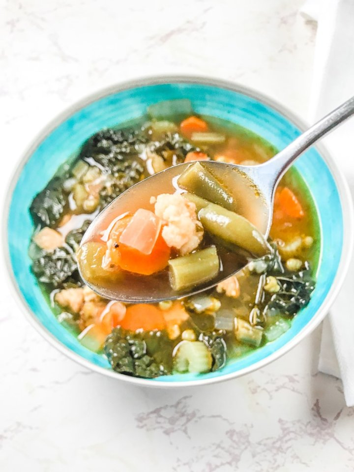 Bite of instant pot chicken vegetable soup on a spoon.