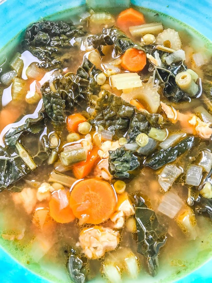 Close up of pressure cooker chicken vegetable soup showing the kale, carrots, peas, and chicken.