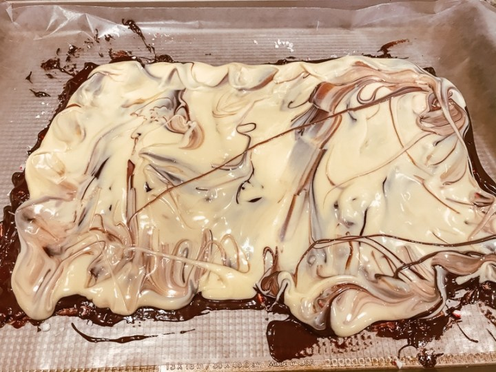 White chocolate spread over melted semi sweet chocolate on a cookie sheet.