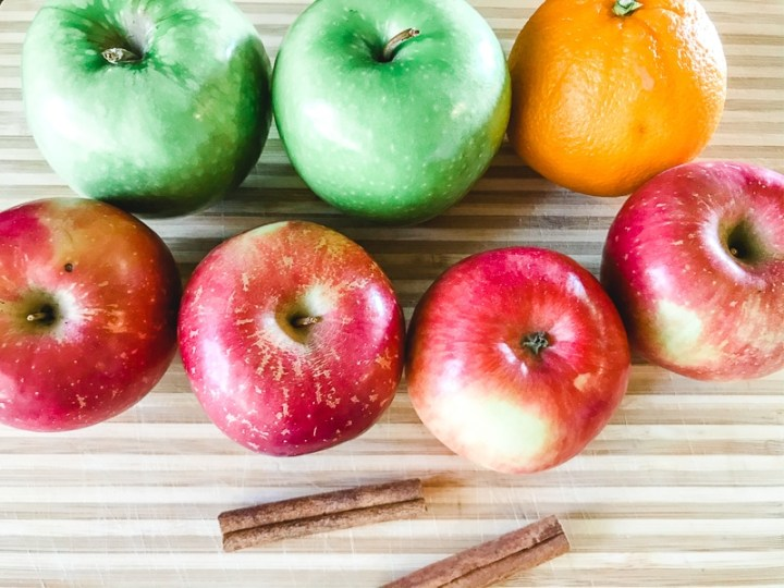 A cutting board filled with red and green apples, an orange, and two cinnamon sticks.