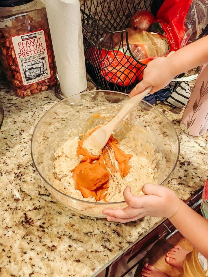Little hands mixing pumpkin puree into the pumpkin cornbread batter.
