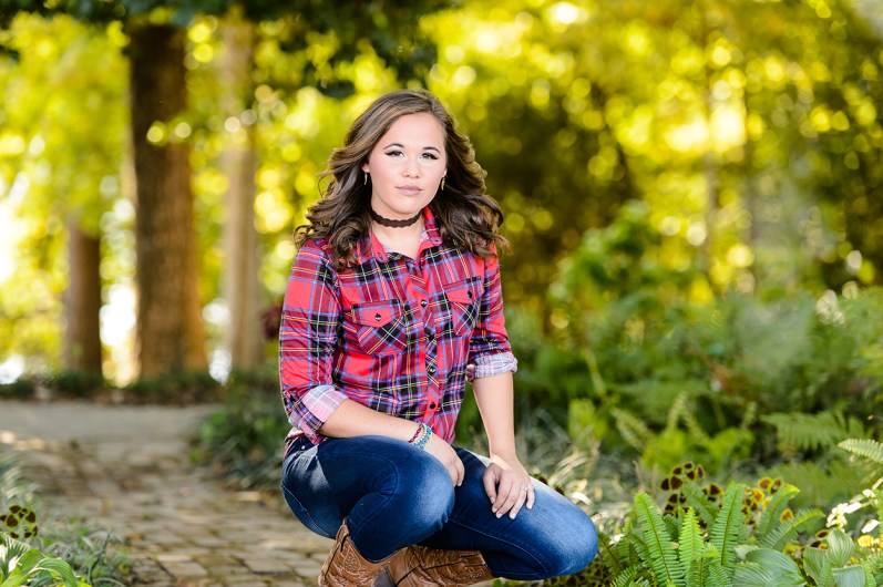 Brunette with choker and plaid shirt poses outdoors