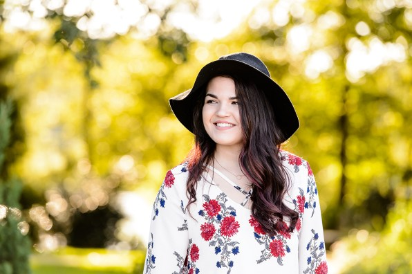 Brunette with choker and floral shirt with hat poses outdoors