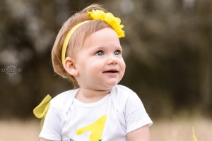 little blonde girl standing in field in yellow tutu and yellow flowered headband