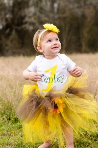 little girl in field smiling wearing a yellow tutu and flowered headband