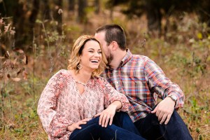 middle georgia engagement session couple in pink and blue jeans sitting in field laughing and holding each other