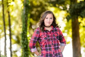 girl standing in field wearing red shirt and blue jeans for senior portrait session