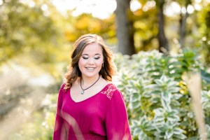 senior photography session, brown haired young lady standing in garden looking down and smiling during her senior portrait session at tryphenas garden wedding venue in middle georgia, middle georgia photographer