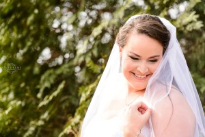 middle georgia wedding, bride holding white veil by face during bridal portait in garden