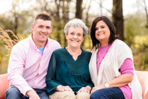 grandmother in green shirt sitting on sofa in field with daughter in pink and white shirt and grandson in pink shirt portrait session