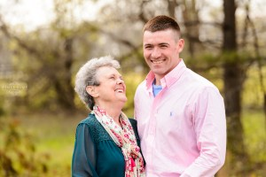 grandmother in green shirt laughing with her grandson in pink shirt during portrait session middle georgia