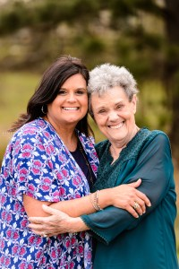 grandmother in green shirt hugging daughter in blue and pink shirt in field in middle georgia during portrait family photosession