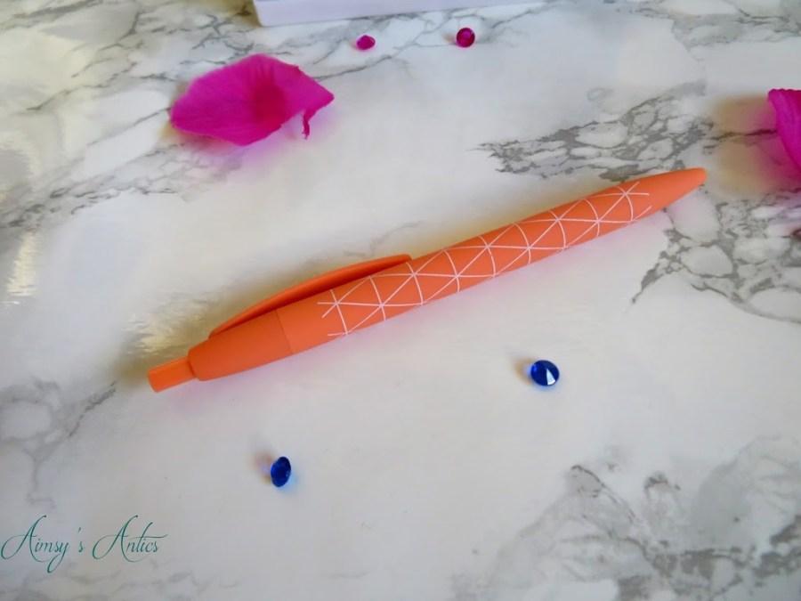 Orange pen with white diagonal print.