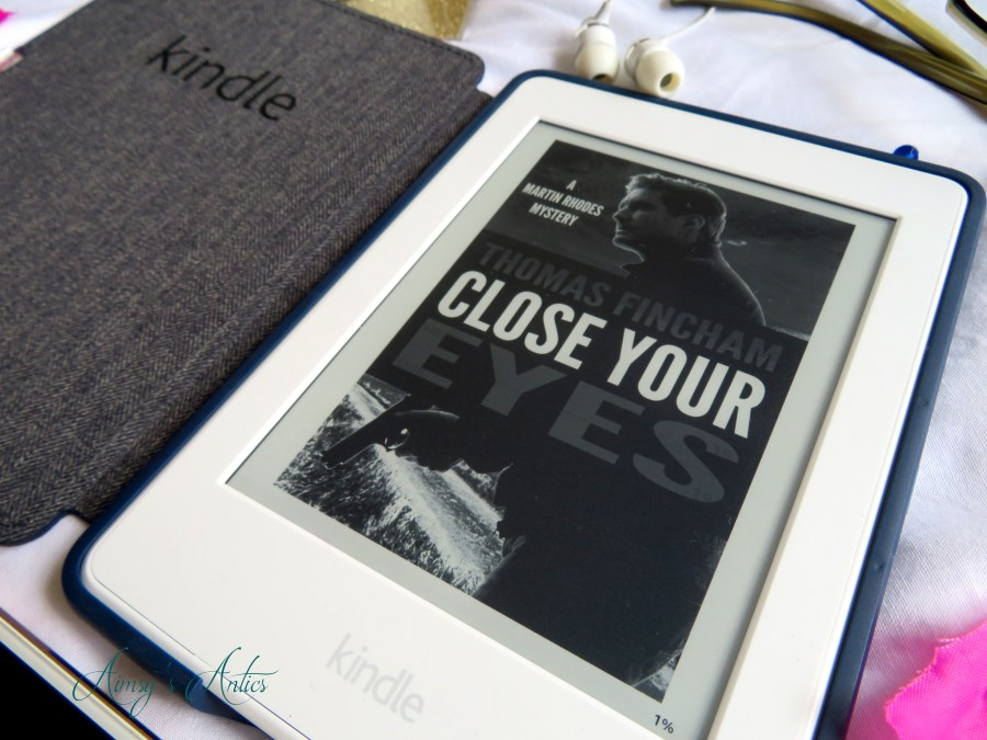 A kindle with the 'Close Your Eyes' book cover displayed on it.