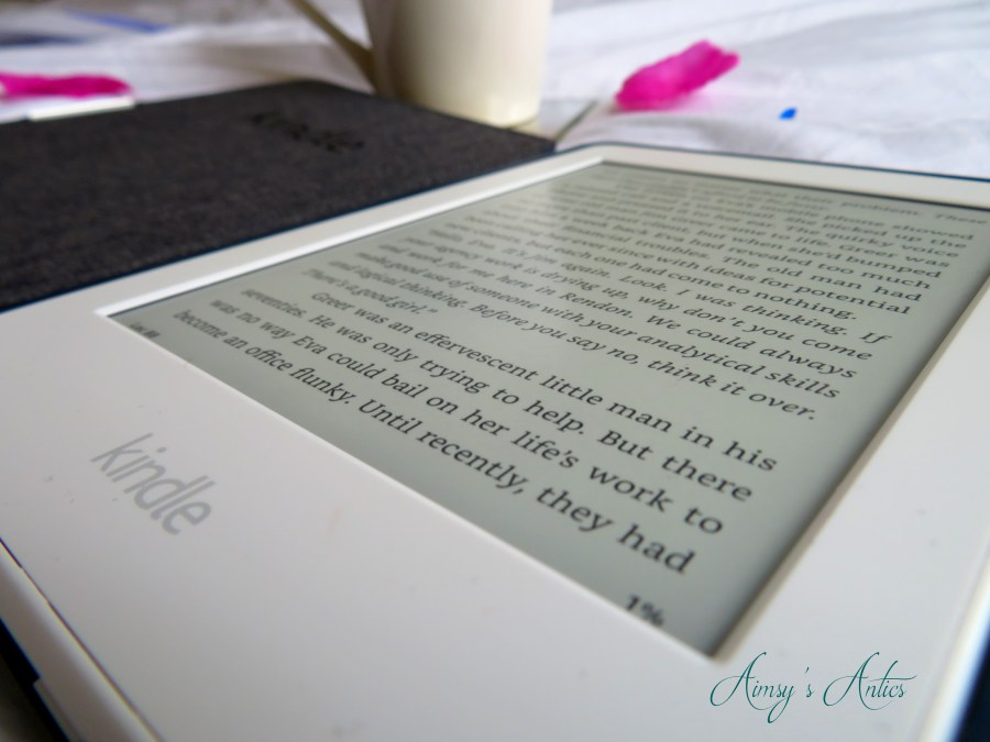 Close up of a Kindle with a cup in the background