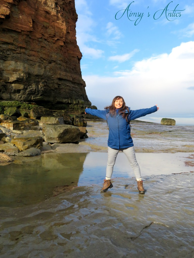 A woman standing on the rocks with arms spread out in Staithes