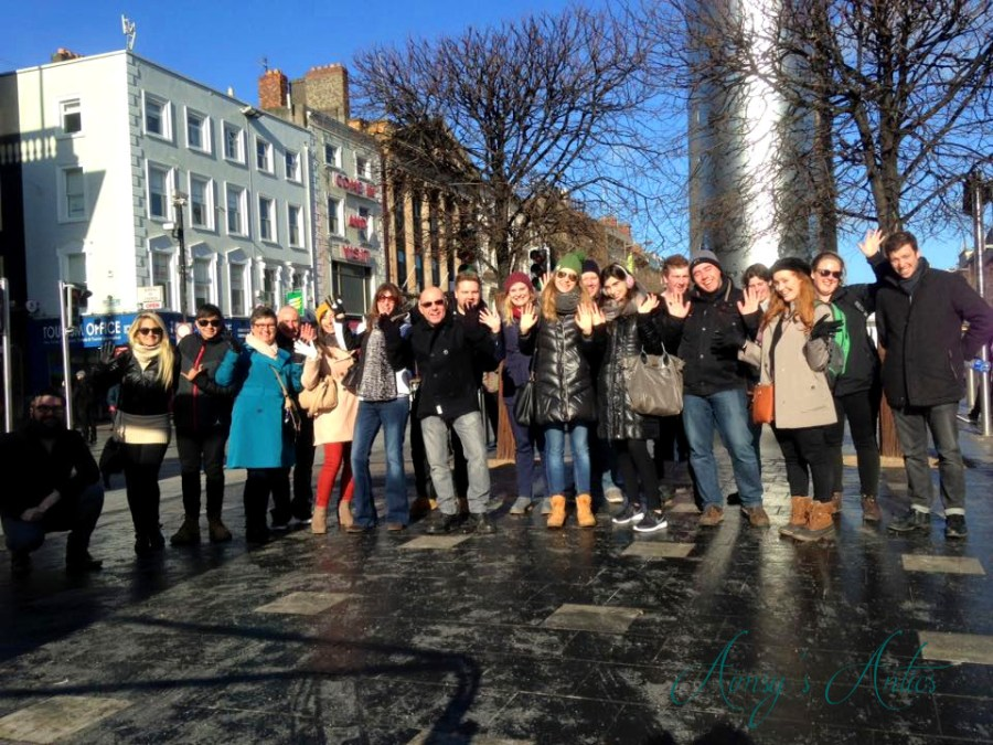 A group of people on Dublin free walking tour, in front of the Spire.