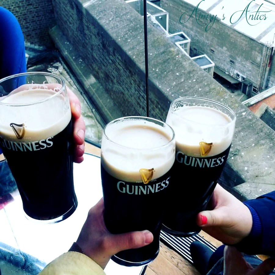 Three pints of Guinness being held in hands